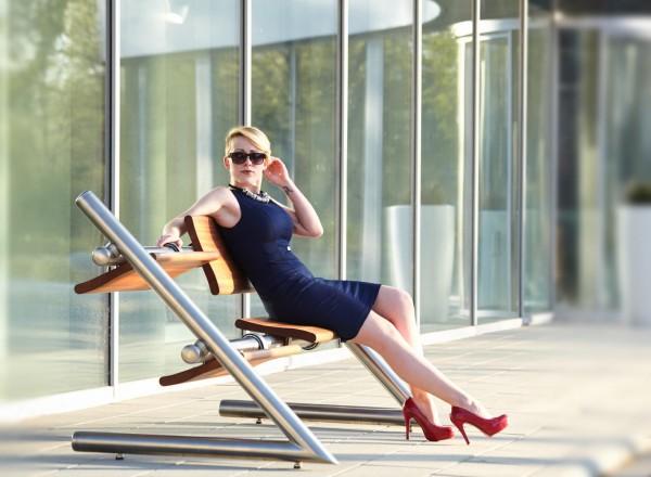 Frau sitzt auf Wendebank aus Edelstahl XL
